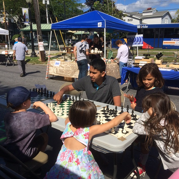 President Sandeep Alampalli teaching chess at the Fair